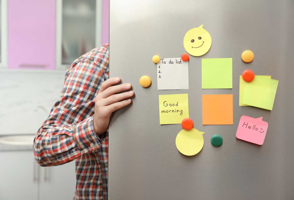 man in plaid shirt holding open fridge door with colorful notes and magnets on the door