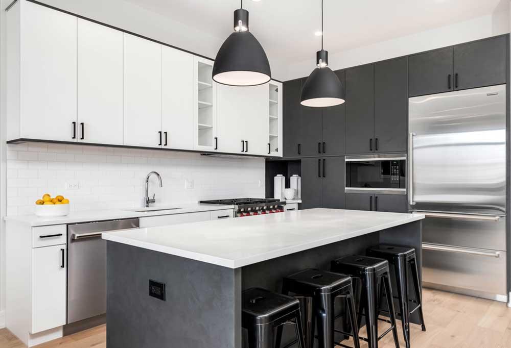 Modern kitchen with half white cabinets and half dark gray with a stainless steel Sub- Zero fridge