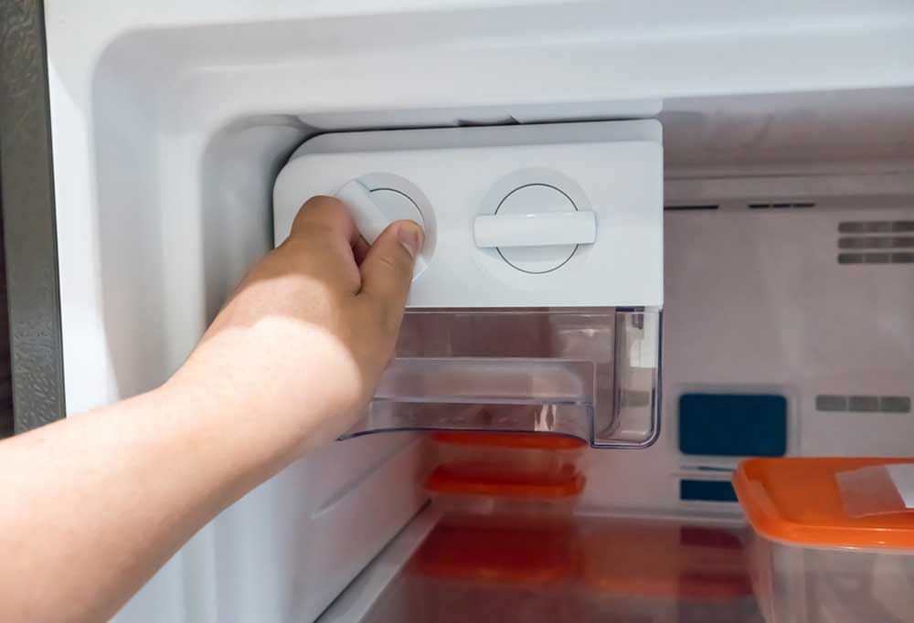 Hand adjusting thermostat dials in a fridge.