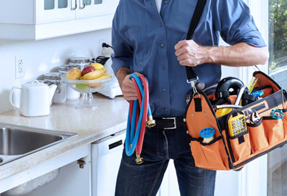 Man holding hot and cold water line with a packed tool bag on hi shoulder.