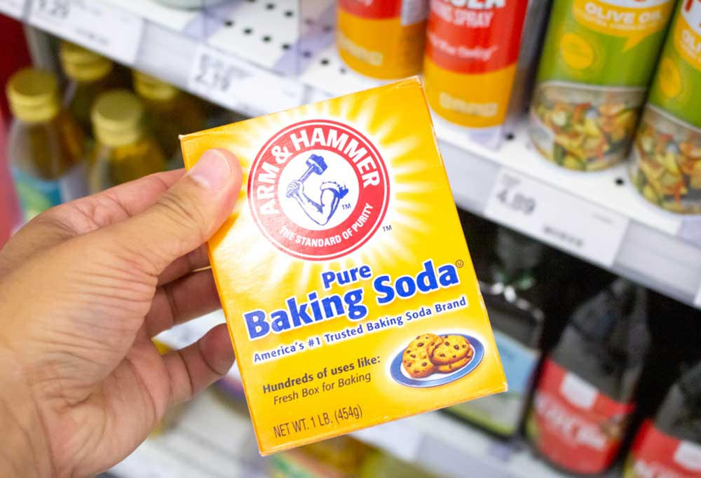 Hand holding a box of baking soda in a super market