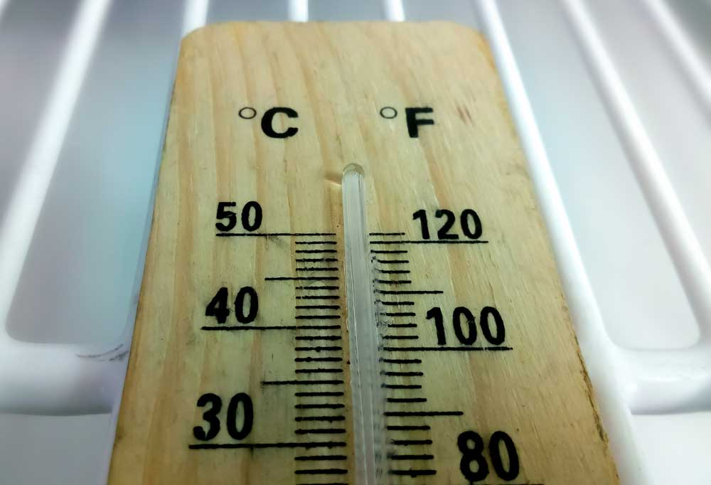 Wooden thermometer with black writing laying on a fridge shelf