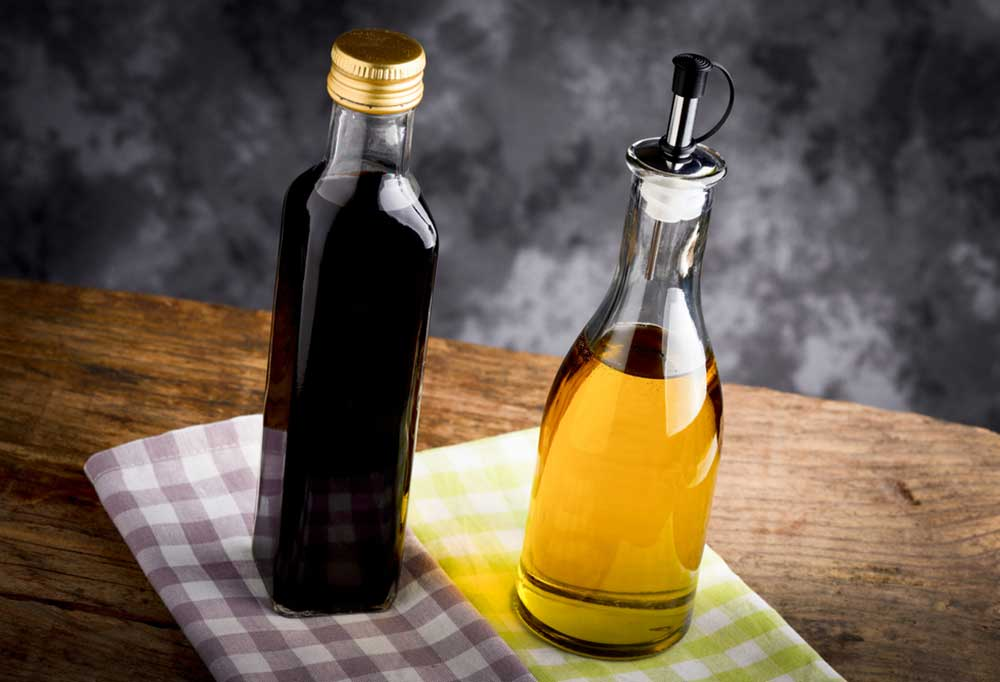 A bottle of oil and a bottle of vinegar on checkered teat towels on a wooden surface