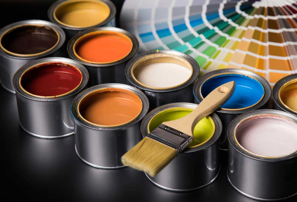 Variety of colors of paint in metal cans with fanned out paint color sample cards and a paint brush laying over the green paint all on a black surface.