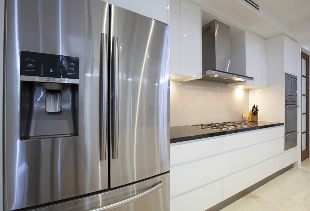 Very shiny stainless steel fridge in a white kitchen