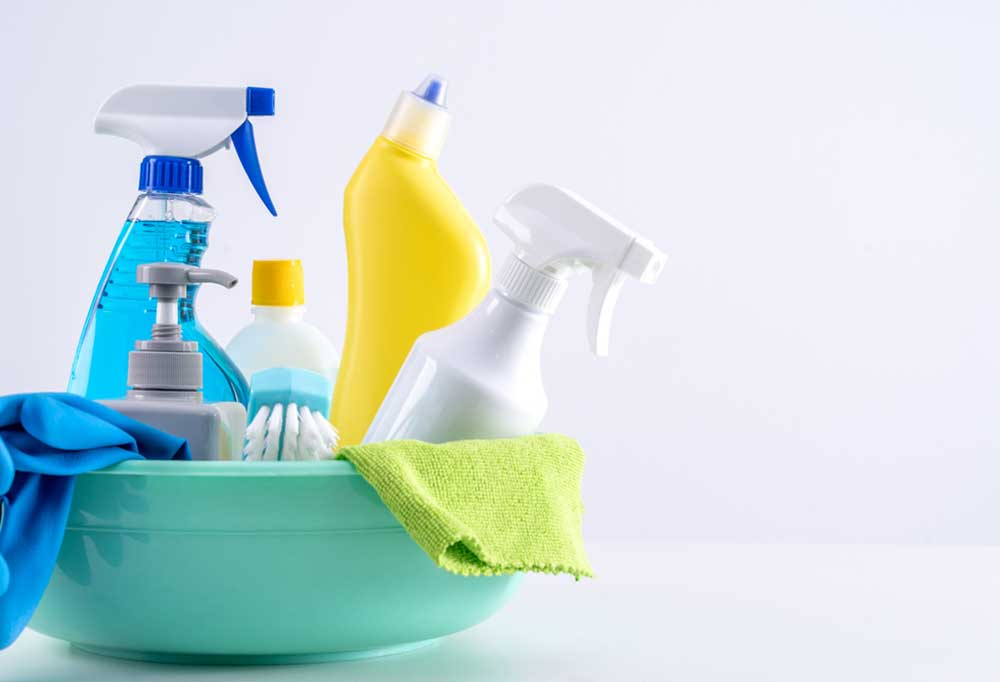 Teal colored bowl full of cleaning supplies on a white background