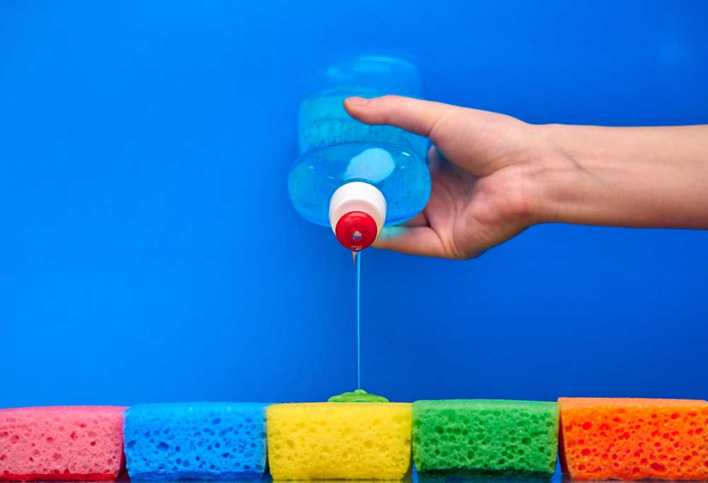 Dish washing liquid being poured on different colored sponges against a blue backgound