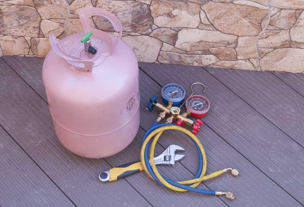Pink bottle of Freon with gages, hoses, and tools, on a deck