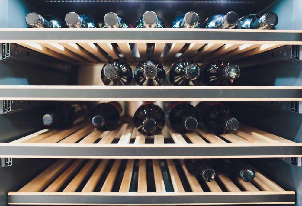 Wooden slatted shelves in a wine fridge full of wine.