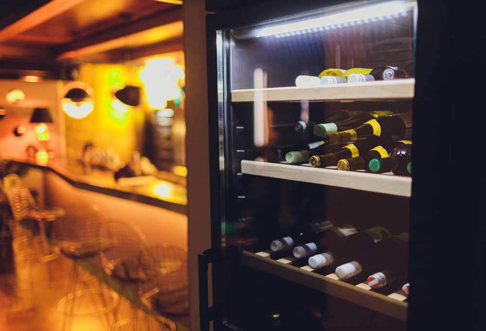 Close up  of a wine fridge with a bar in the background