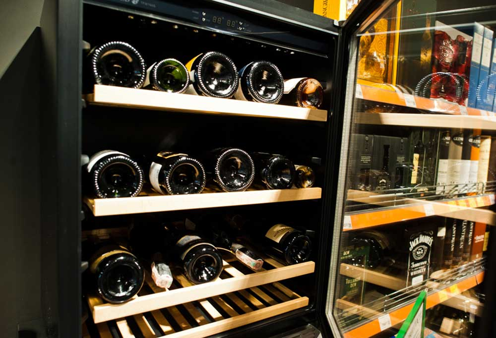 Close up of an opened wine fridge with the bottom of the bottles pointing forward.
