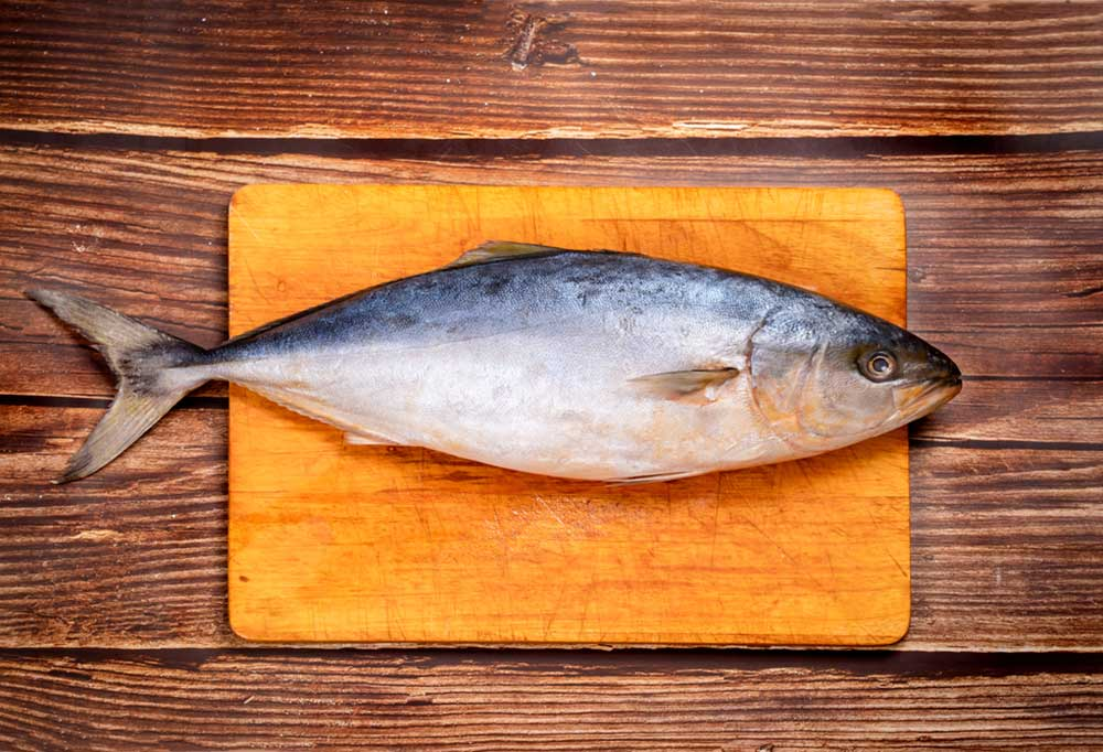 Whole fish lying on a wooden plank on a darker wood table.