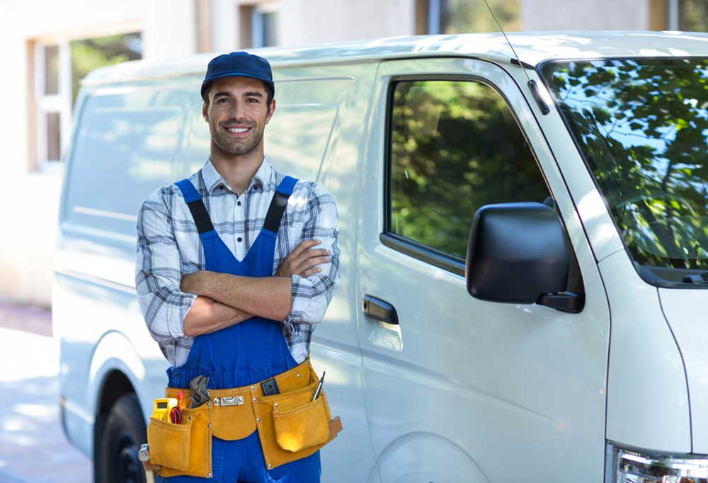 Repair man in a plaid shirt and blue coveralls with arms folded across chest standing next to a white van.