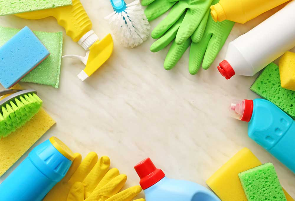 Variety of cleaning supplies bordering the edge of the photo, pointed towards the center.