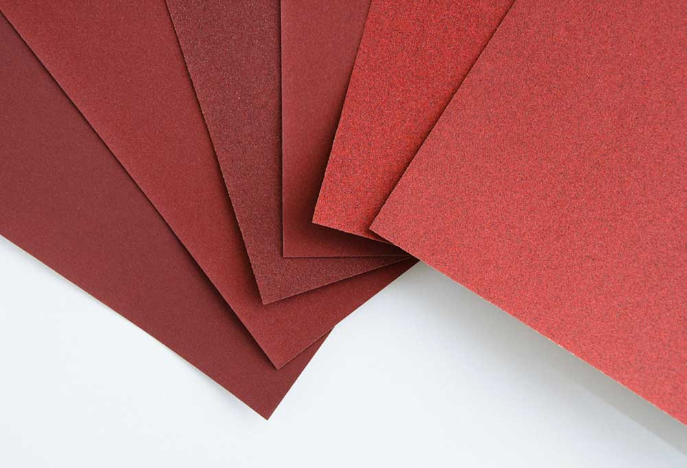 Variety of red sandpaper on a white background