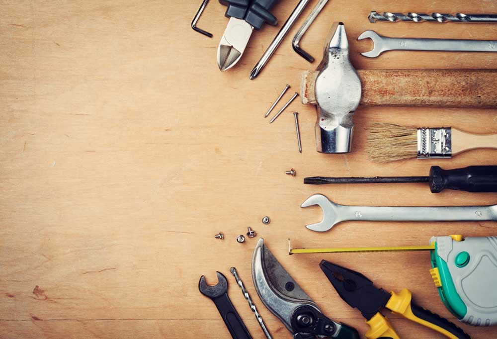 random tools, screws and nails on a wooden surface