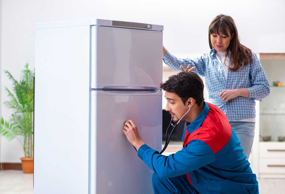 Repair man and homeowner listening to the fridge with a stethoscope
