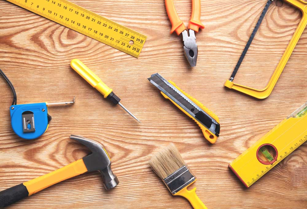 Variety of yellow tools scattered on a wooden board