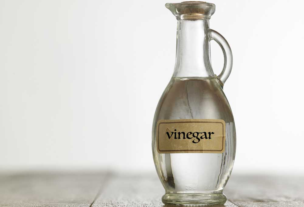 Clear glass bottle with a pouring spout with a label that says Vinegar.