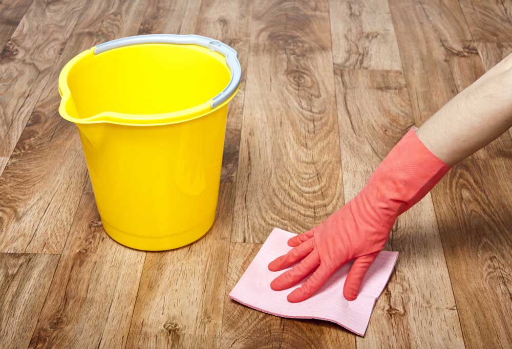Yellow bucket next to a pink gloved hand wiping the floor with a pink rag.