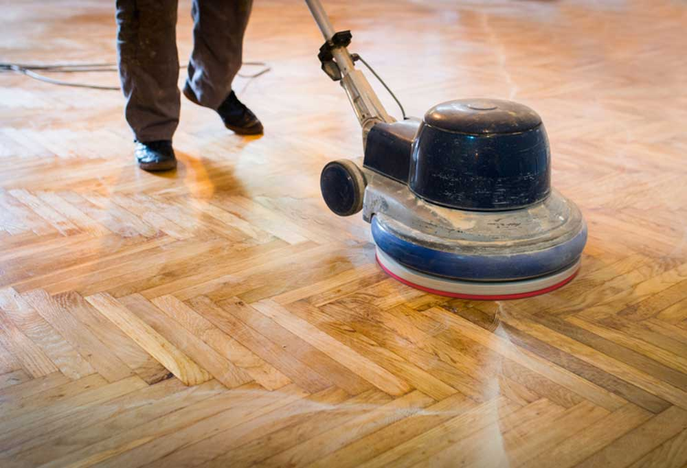 Person buffing hard wood floors with an electric floor buffer