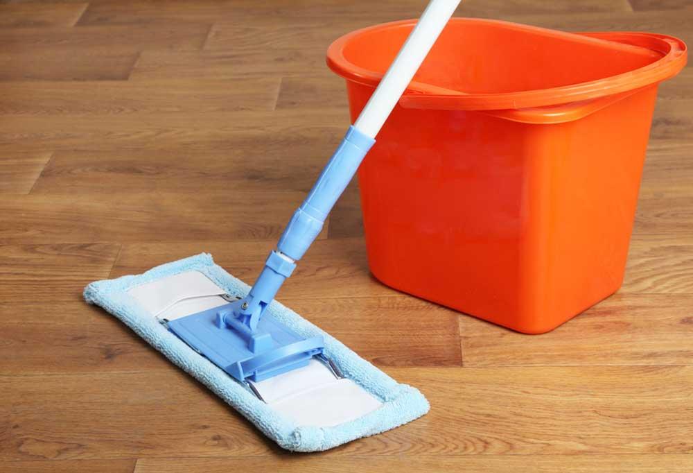 Microfiber rectangle mop leaning on an orange bucket on hardwood floors.