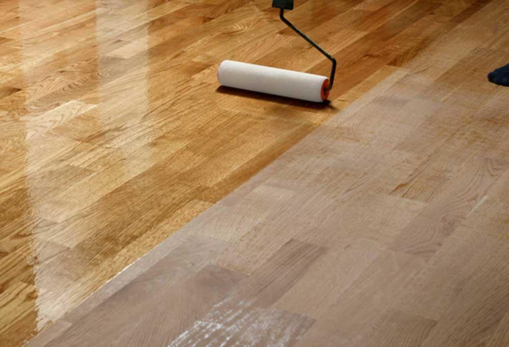Varnish being rolled onto sanded hardwood floors.