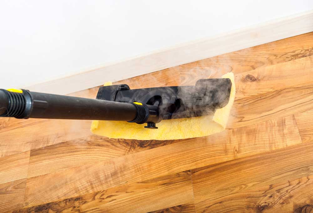 Steam cleaner with a yellow pad steam cleaning hardwood floors