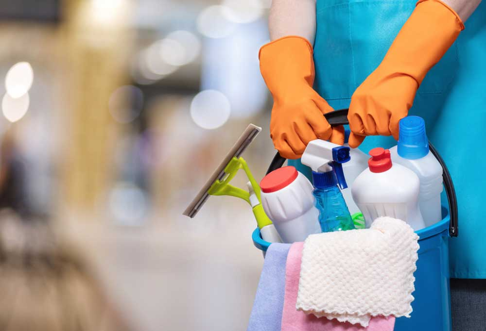 Hands wearing orange rubber gloves holding the handle to a bucket filled with cleaning supplies