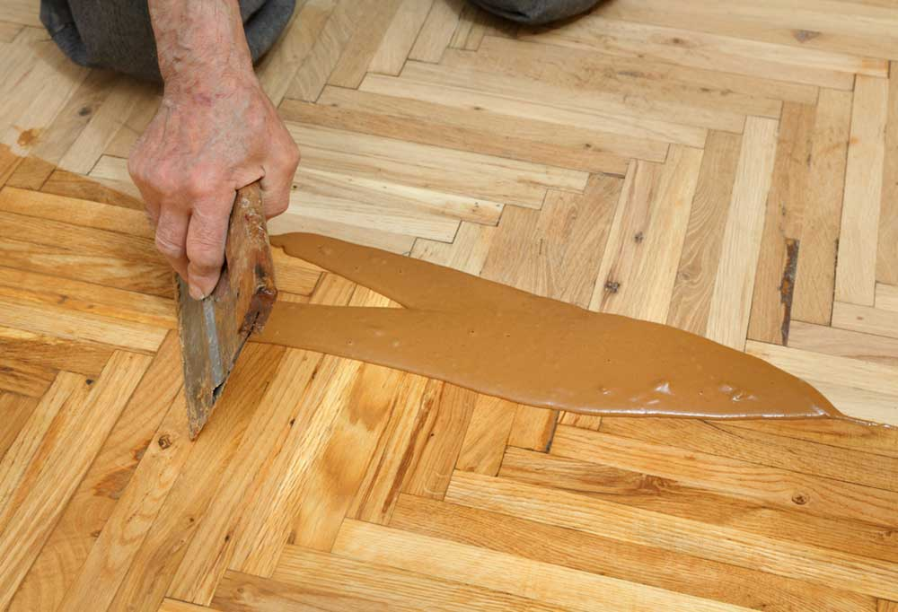 Hand using a scraper to push stain into hardwood floors