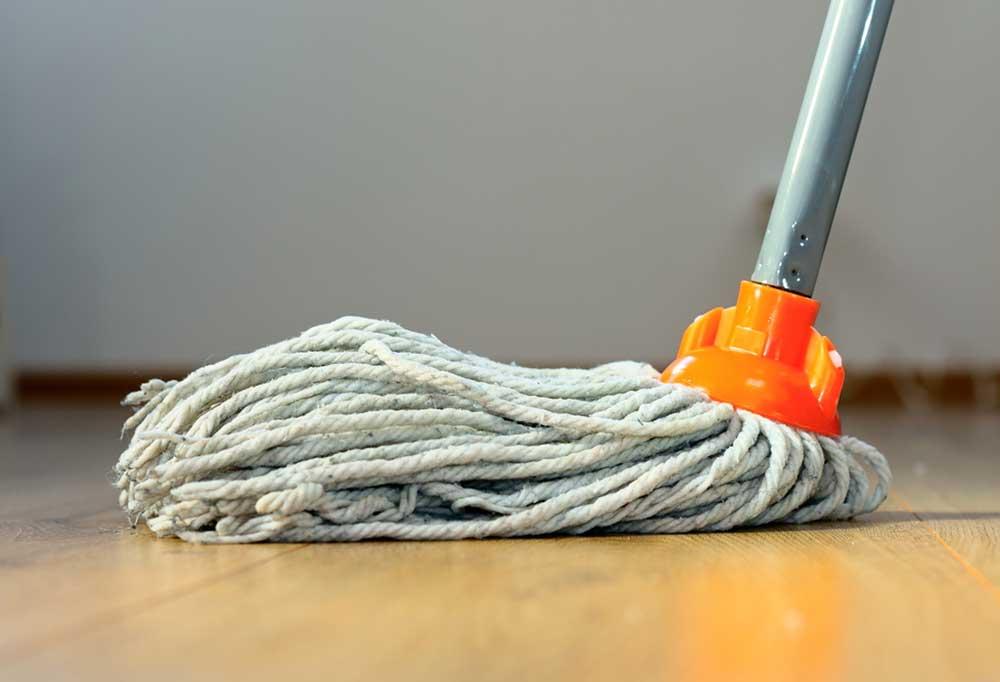 Closeup of a string mop on hardwood floors