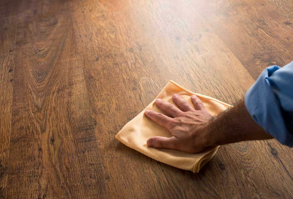 Masculine hand drying hardwood floor with a microfiber cloth