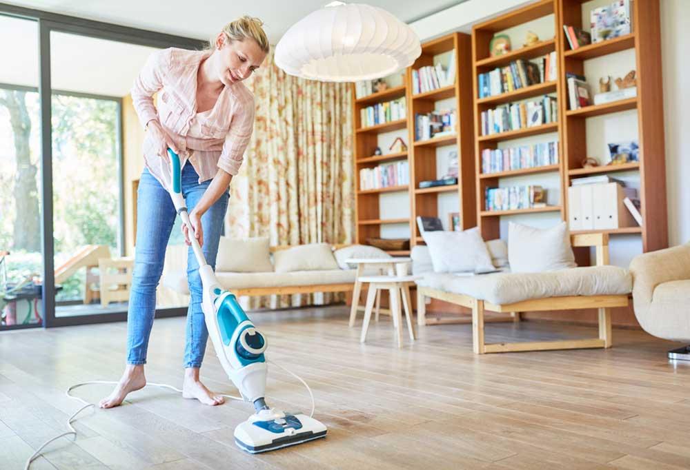 Woman pushing steam cleaner on hardwood floors