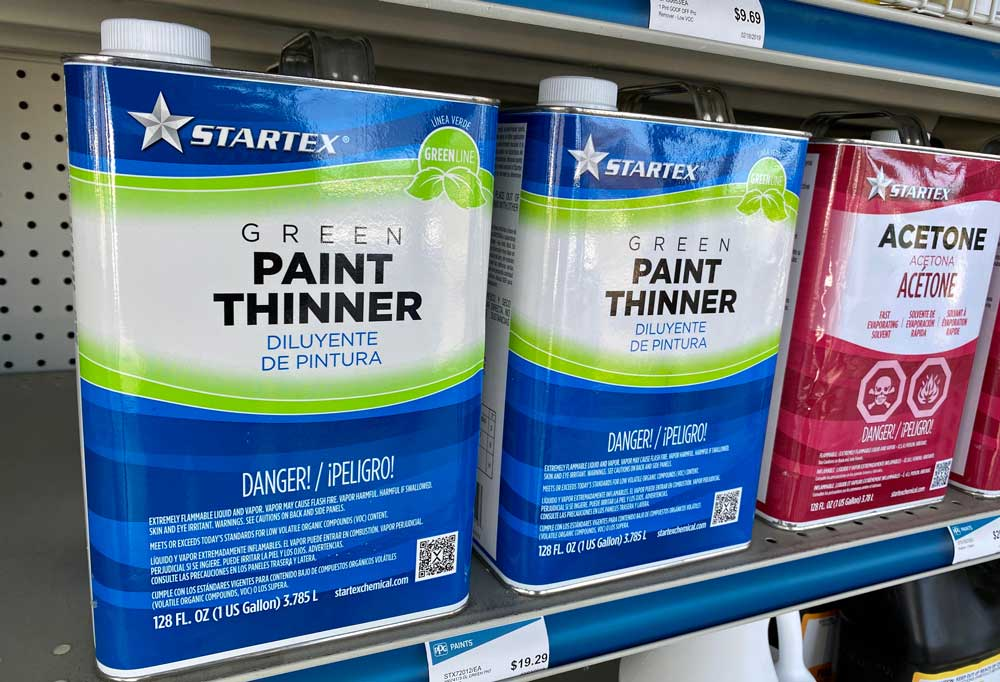 Metal cans of paint thinner on a store shelf