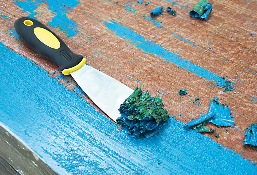 Scrapper being used on hard wood covered in blue paint