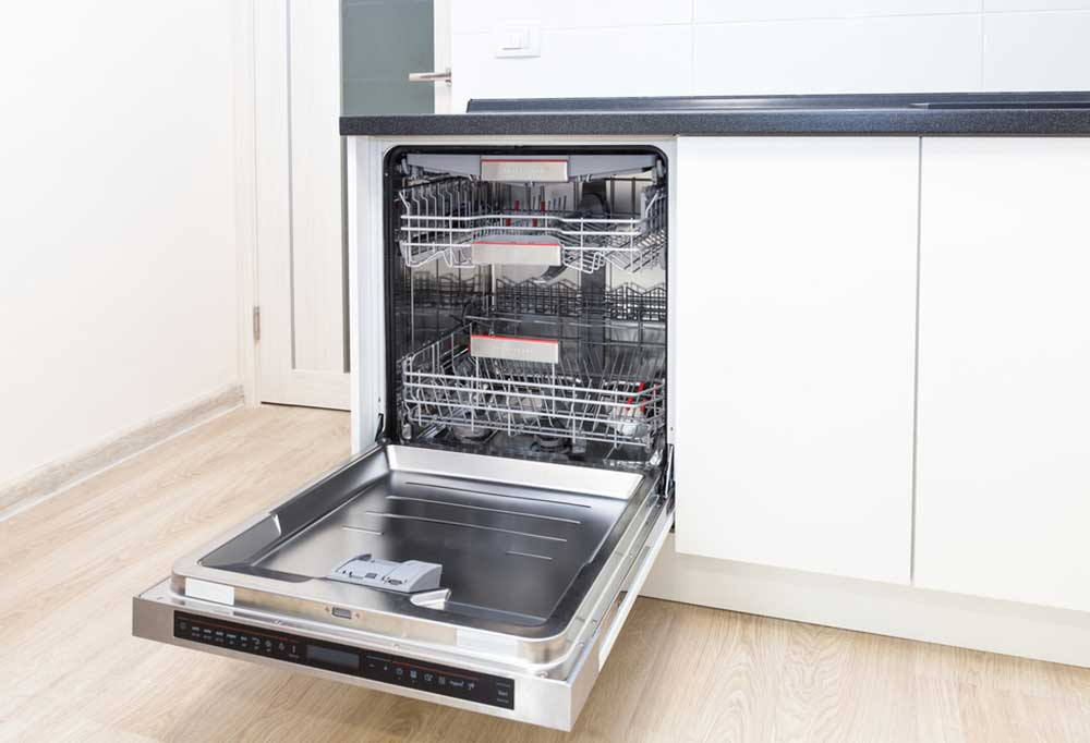 Empty, open dishwasher in a kitchen with hardwood floors and white cabinets