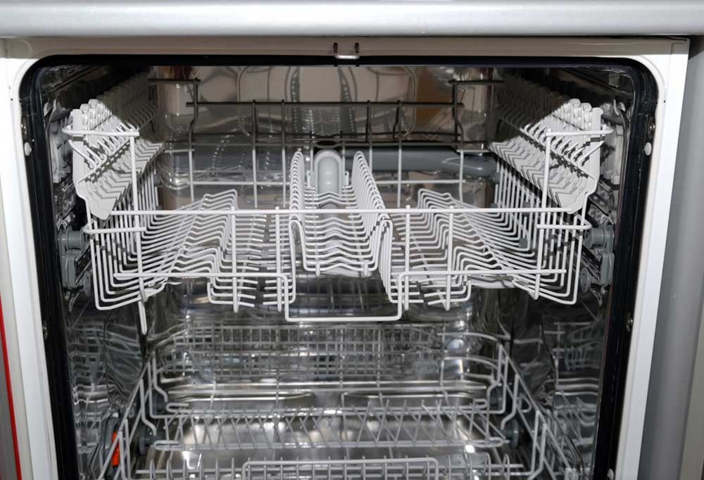 Close up of the shelves in an open dish washer