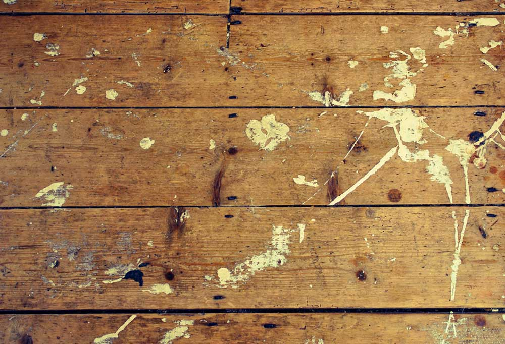Scarred old hardwood floors splattered with paint.