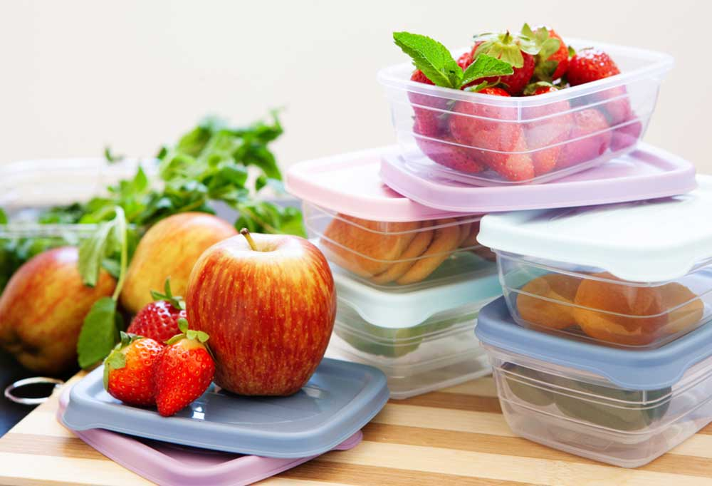Variety of fruits being placed in storage containers