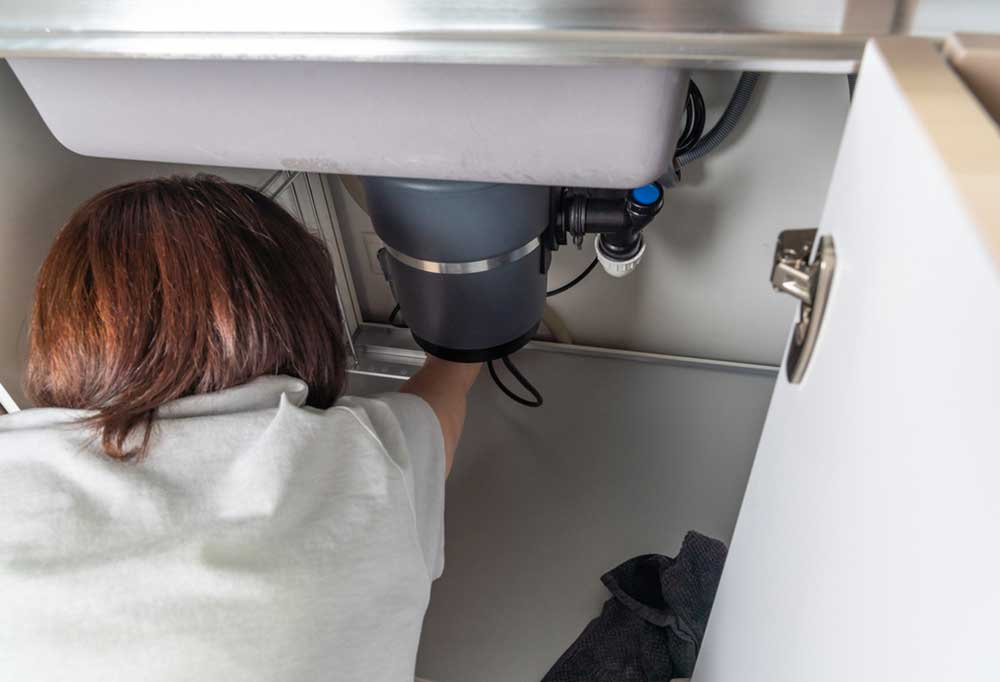 Person underneath the kitchen sink reaching as if cleaning beyond the viewing area