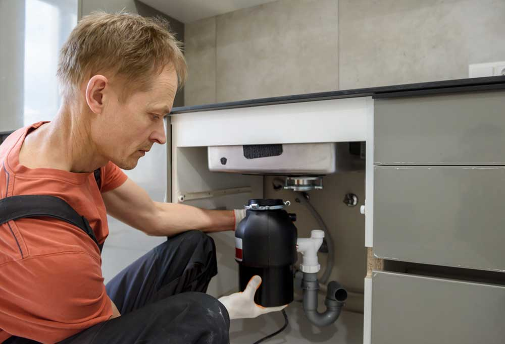 Man in an orange shirt and suspenders installing a garbage disposal under the sink