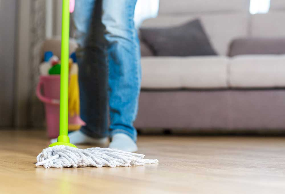 Pair of legs wearing blue jeans mopping hardwood floors with a lime green mop with a bucket and couch in the background.