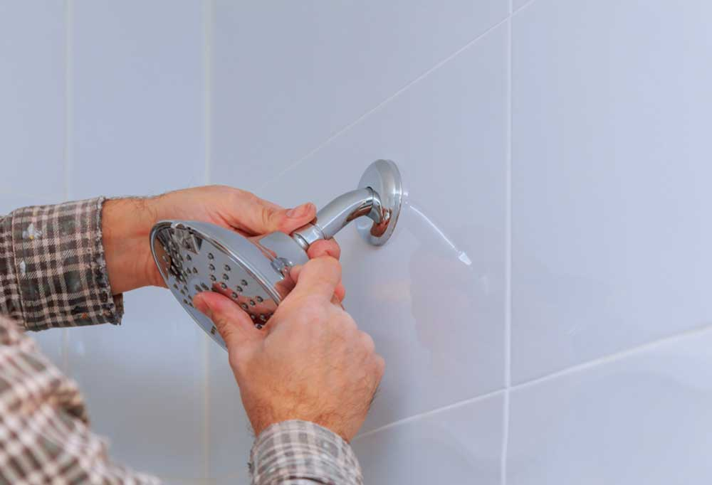 Man in plaid shirt removing shower head from tiled shower stall