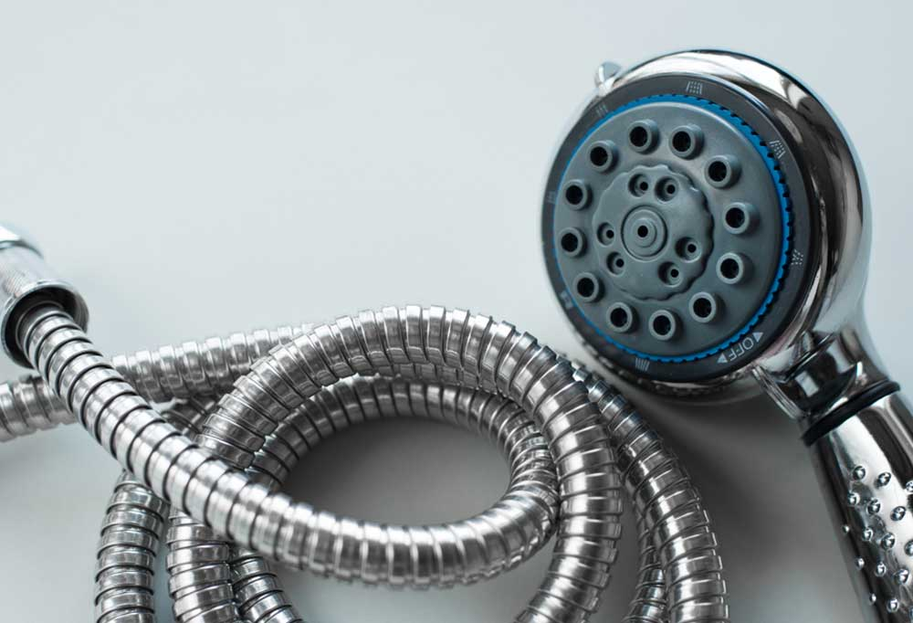 New shower head with a coiled hose isolated on a grey background